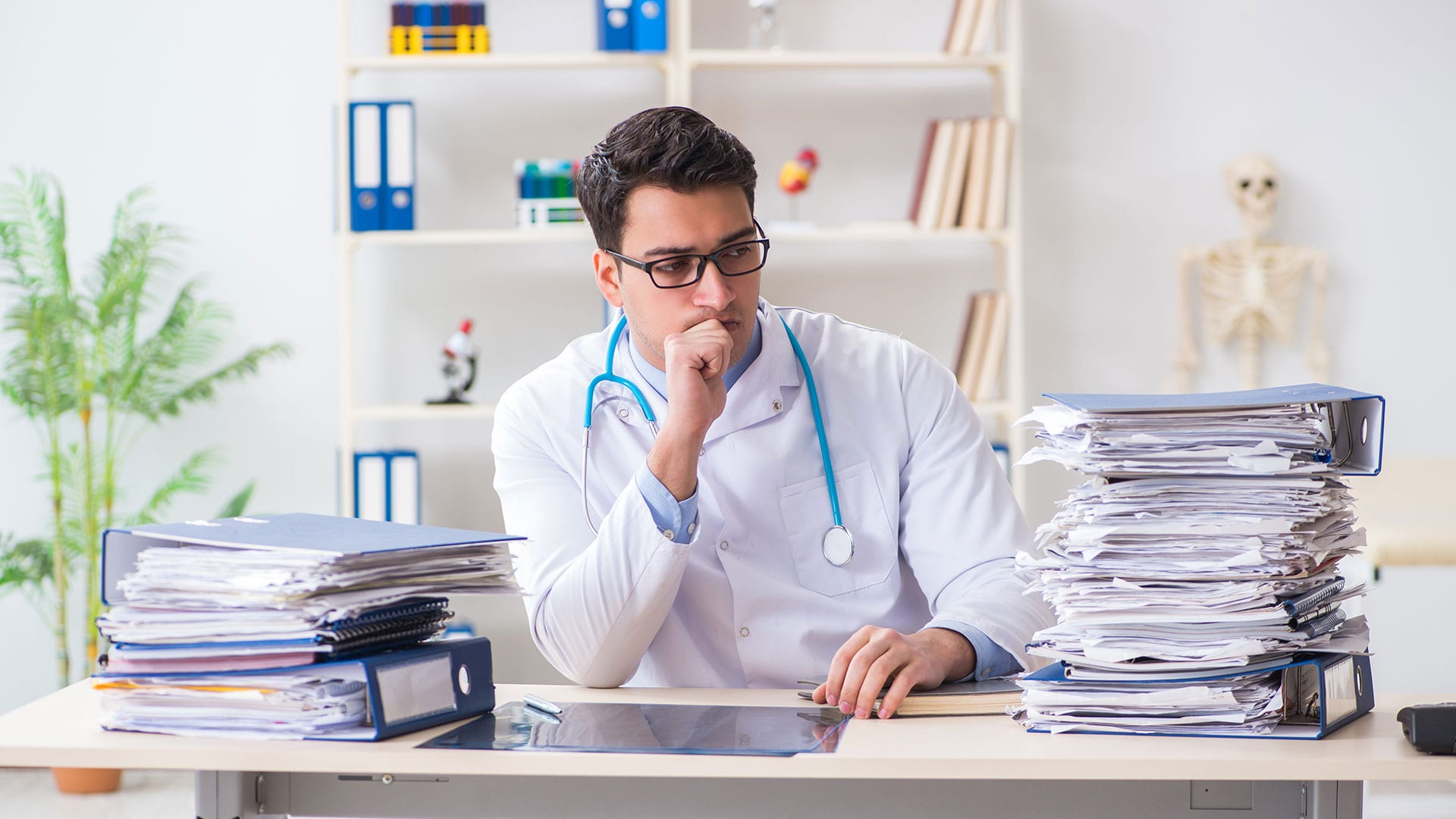 medical doctor with a pile of charts on his desk